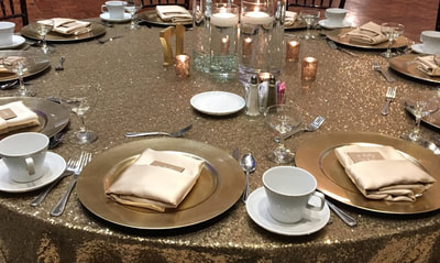 circular table with gold table cloth and gold place settings