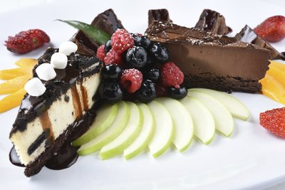 two slices of cake on top of sliced apples and assorted fruit