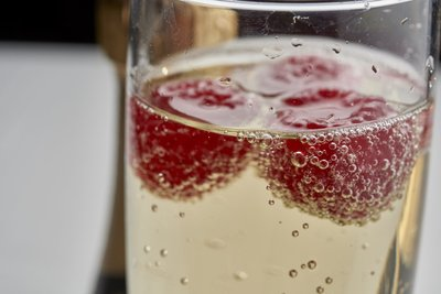 glass of champagne with raspberries floating at the top